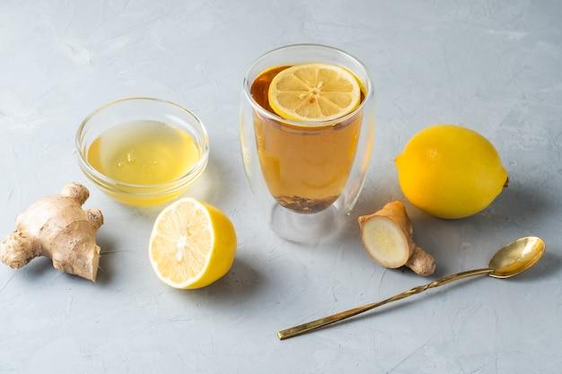 灰色の表面に生姜の根を持つ健康的な生活ハーブティーレモンハニーティー