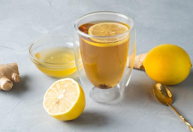 灰色の表面に生姜の根を持つ健康的な生きているハーブティーレモンハニーティー