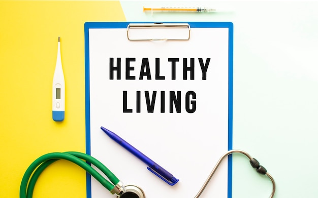 Healthy living text on a letterhead in a medical folder on a beautiful background. stethoscope, thermometer and pen.