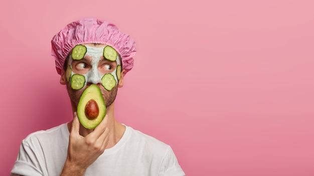 건강한 모습. 잠겨있는 젊은 유럽 남자가 아보카도의 절반으로 입을 덮고 얼굴에 오이로 보습 크림을 바릅니다.