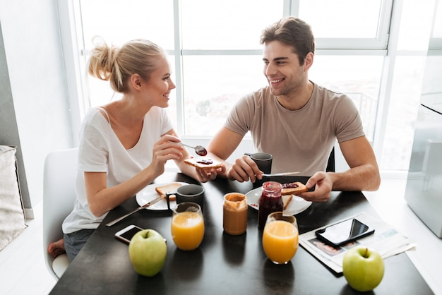Healthy lovers sitting in kitchen and eating breakfast