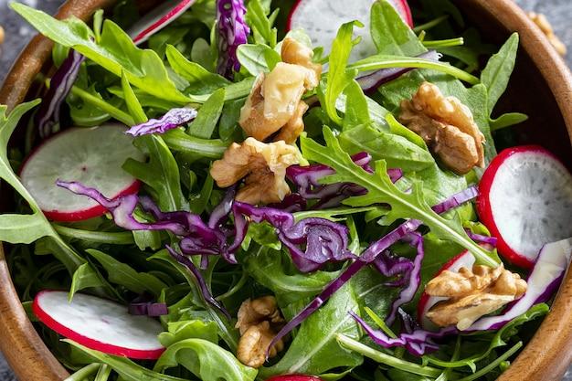 Здоровый низкокалорийный салат с рукколой, редисом, красной капустой и грецкими орехами крупным планом