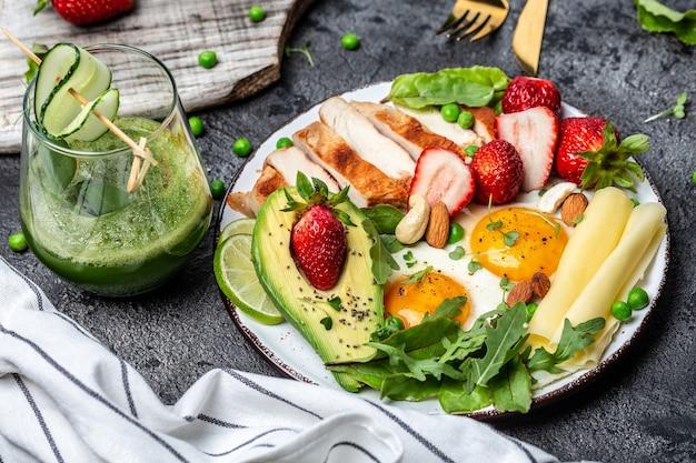 健康的な低炭水化物製品。目玉焼き、アボカド、ストロベリー、チキンフィレのグリル、チーズ、ナッツ、ルッコラ、デトックススムージー、フレッシュグリーン。ケトジェニックダイエットの概念。上面図。