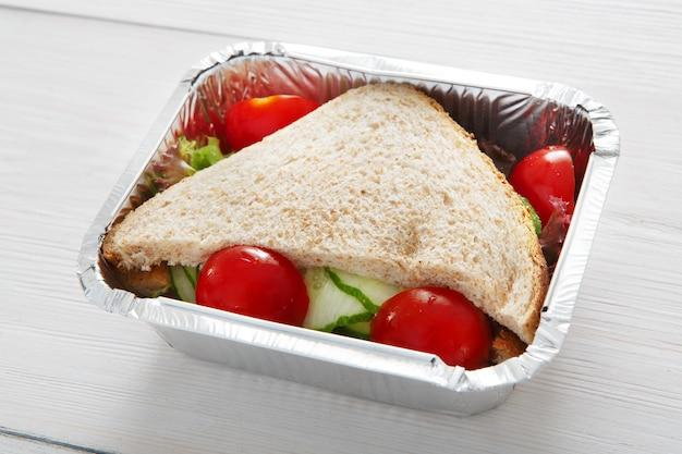 健康的なランチとダイエットのコンセプト。食べ物を持ち帰ります。ホワイトウッドの全粒粉パン、キュウリ、トマトのサンドイッチ