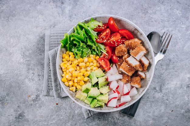 Healthy lunch bowl. avocado, chicken, tomato, radish, corn, green leaves vegetables salad.