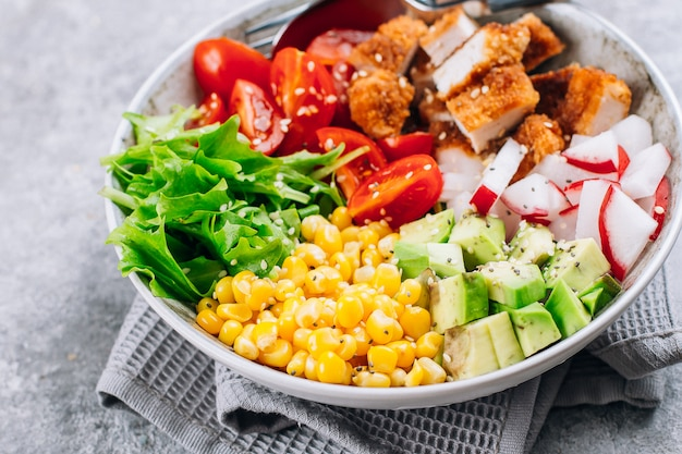 Healthy lunch bowl. avocado, chicken, tomato, radish, corn, green leaves vegetables salad