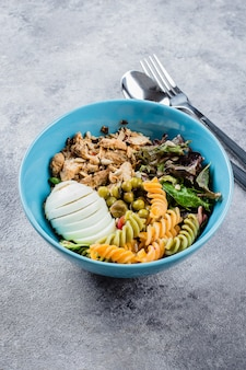 Healthy lunch bowl. chicken, pasta fusilli, mix greens, green peas on concrete background