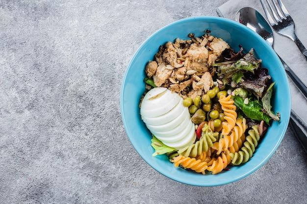 건강한 도시락. 닭고기, 파스타 Fusilli, 콘크리트 배경에 혼합 채소, 완두콩 프리미엄 사진