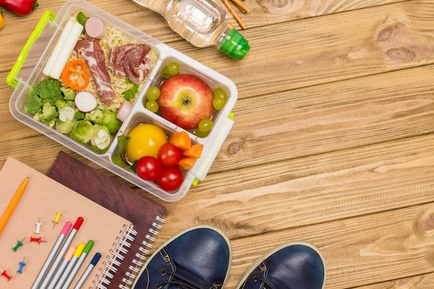 Healthy lunch box and colorful stationery with blue shoes