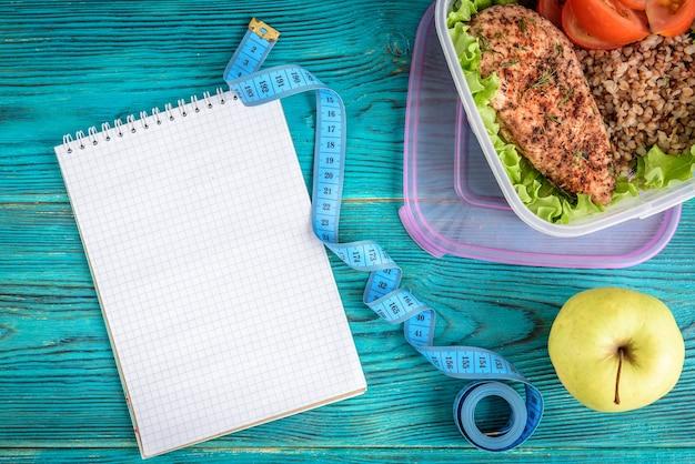 Здоровый ланч-бокс с жареной куриной грудкой, гречкой и помидорами и бутылкой воды на синем деревянном фоне.