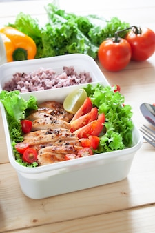 Healthy lunch box with grilled chicken, lime, tomatoes and lettuce, served with steam rice