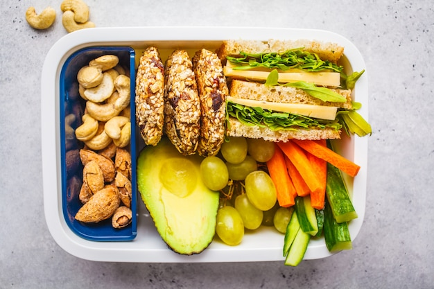 Healthy lunch box with sandwich, cookies, fruits and avocado on white background.