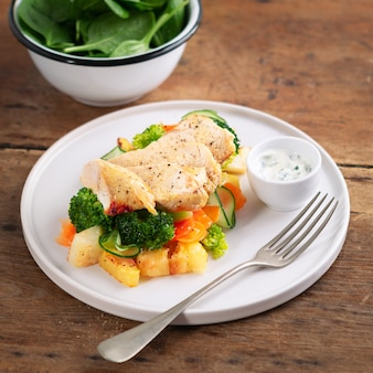 Здоровый обед, ужин. здоровая запеченная куриная грудка с овощами, жареным картофелем, огурцом, морковью, брокколи и шпинатом на тарелке в деревенском стиле.