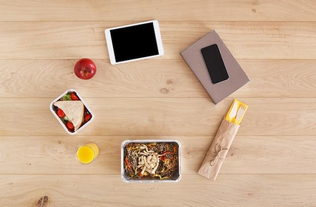 건강한 점심-샌드위치가있는 호일 상자, 칠면조, 사과, 오렌지 주스 및 테이블에 나무 칼 붙이가있는 현미 당면.