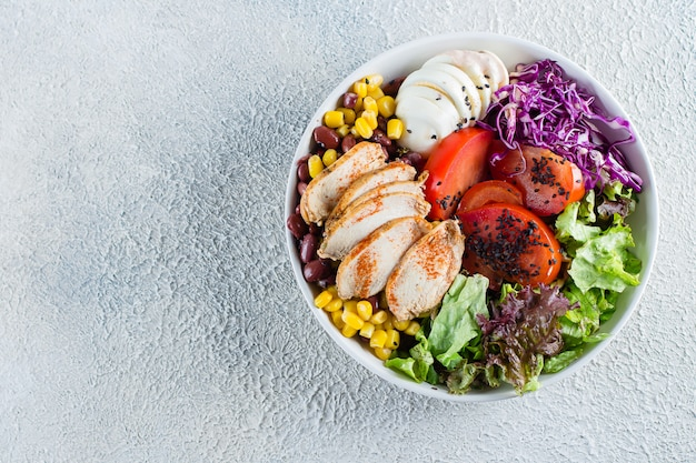 Healthy lunch salad with chicken, egg, vegetables and barbeque sauce on light concrete background