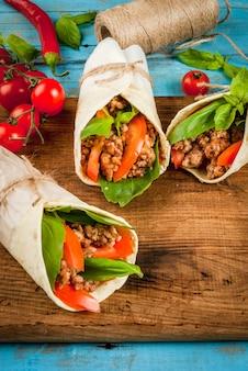 Здоровый обед, перекус. бутерброды витой рулет tortilla с говядиной и овощами деревянная разделочная доска на синий деревянный деревенский стол, копией пространства, вид сверху