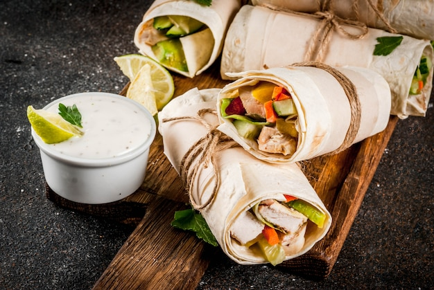 Healthy lunch snack stack of mexican street food fajita tortilla wraps with grilled buffalo chicken fillet and fresh vegetables