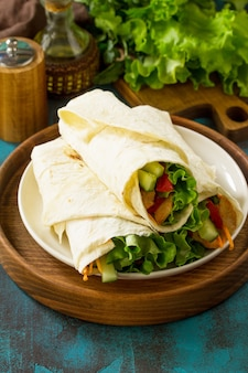 Healthy lunch snack tortilla wraps with grilled chicken and  fresh vegetables on blue table
