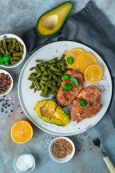 灰色の背景にアボカド、鶏胸肉、豆を使ったヘルシーなランチ。