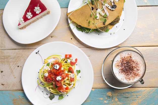 Healthy lunch, zucchini pasta, vegetable crepe and cappuccino coffee, on wooden table, top view.