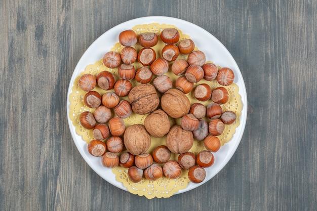 하얀 접시에 건강한 마카다미아 견과류와 호두 고품질 사진