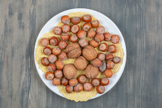 Healthy macadamia nuts and walnuts on a white plate high quality photo