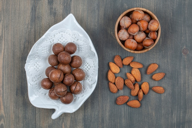 木製のテーブルにアーモンドと健康的なマカダミアナッツ