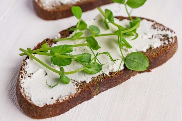 Здоровый макробиотический завтрак. бутерброд со сливочным сыром и горошком в микрогринах.