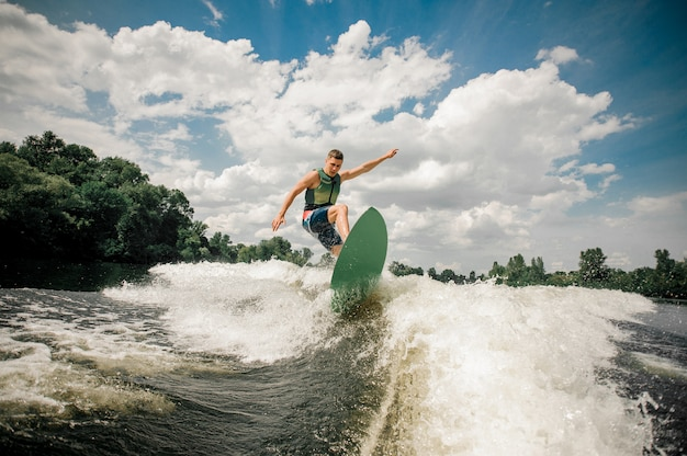 Healthy male rides the waves in a summer river
