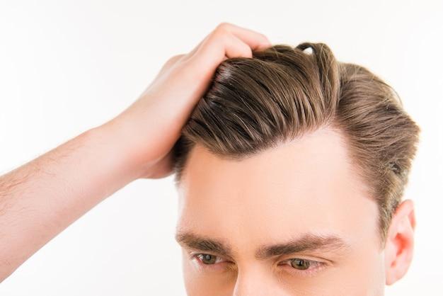 Здоровый мужчина расчесывает волосы пальцами