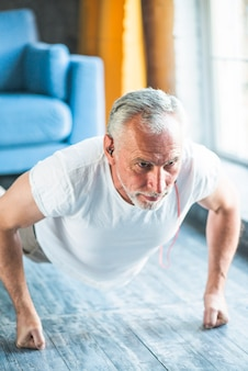 Healthy man doing pushup on hardwood floor at home