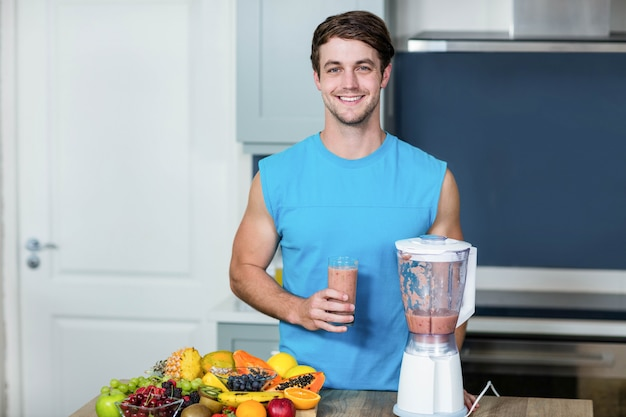 Healthy man preparing a smoothie in the kitchen