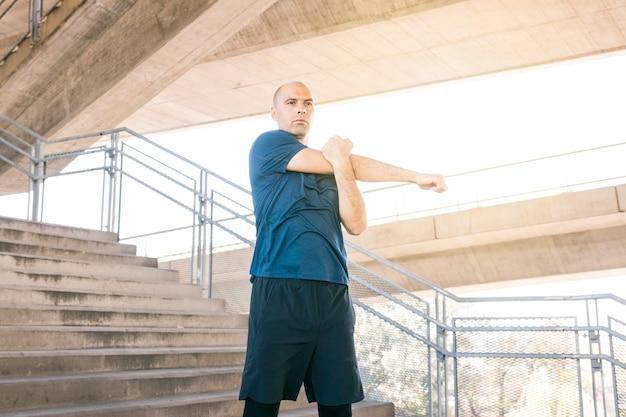 Healthy man standing on staircase stretching his hand