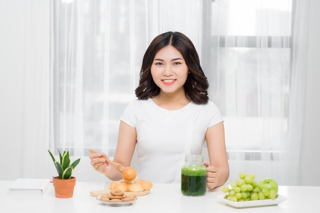 健康食。緑のデトックス野菜のスムージーを飲む幸せな美しい笑顔の女性。健康的なライフスタイル、食事、食事。ジュースを飲む。ダイエット、健康、美容のコンセプト。