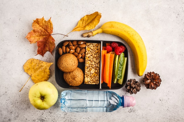 Healthy meal prep containers to school with cereal bar, fruits, vegetables and snacks. takeaway food on white background, top view.