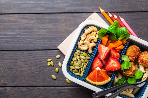 Healthy meal prep containers with beans meatballs, pasta, vegetables, berries, seeds and nuts in a container