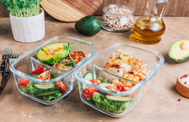 Healthy meal prep containers with chickpeas, chicken, tomatoes, cucumbers and avocado