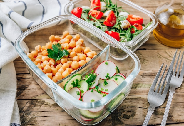Healthy meal prep containers with chickpeas and spring salad