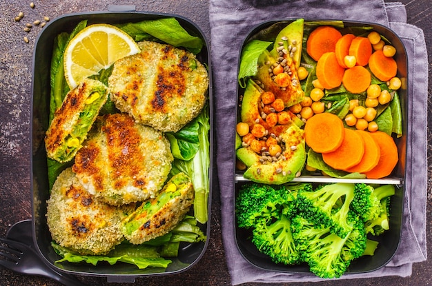 Healthy meal prep containers with green burgers, broccoli, chickpeas and salad on