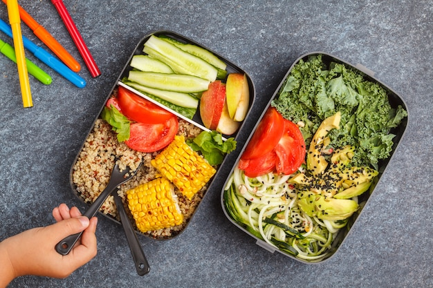 Healthy meal prep containers with quinoa, avocado, corn, zucchini noodles and kale.