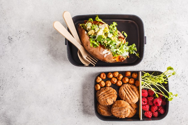 Healthy meal prep containers with quinoa stuffed sweet potatoes, cookies and berries, overhead shot with copy space.
