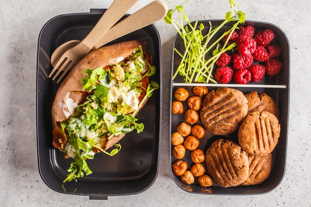 Healthy meal prep containers with quinoa stuffed sweet potatoes, cookies and berries, overhead shot.