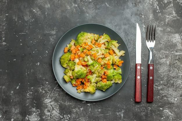 灰色のテーブルの上の黒いプレートにブロッコリーとニンジンの健康的な食事