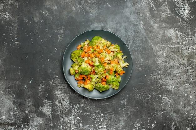 Здоровая еда с броколи и морковью на черной тарелке на сером столе