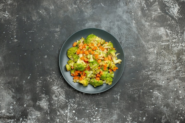 Healthy meal with brocoli and carrots on a black plate on gray table