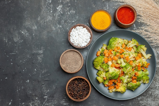 Healthy meal with brocoli and carrots on a black plate and spices on gray table