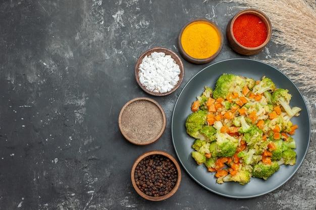 Pasto sano con broccoli e carote su un piatto nero e spezie sul tavolo grigio