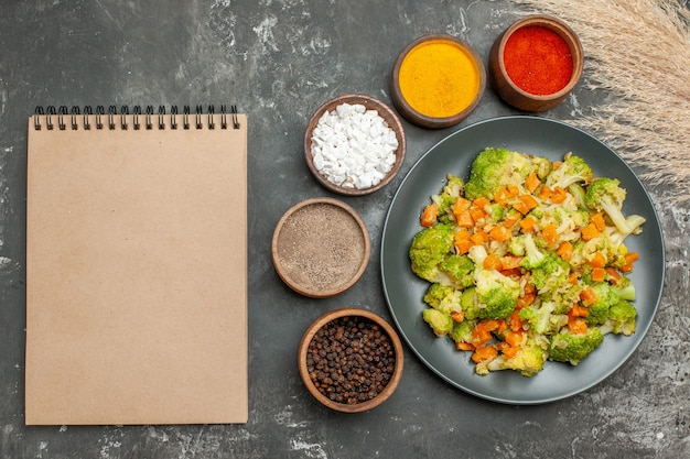 Healthy meal with brocoli and carrots on a black plate and spices next to notebook on gray table