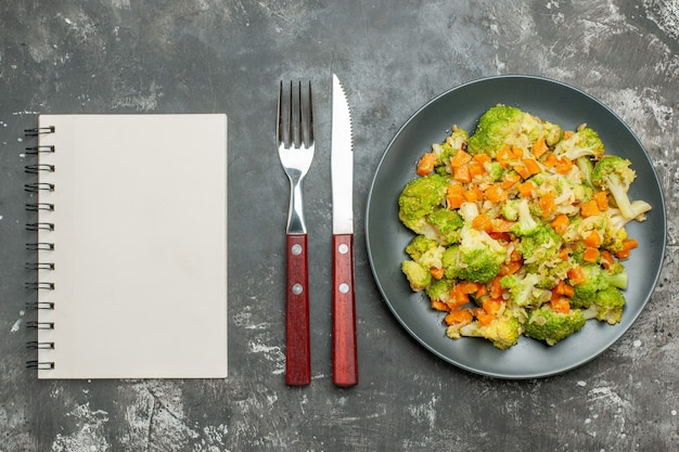 Healthy meal with brocoli and carrots on a black plate with fork and knife next to notebook