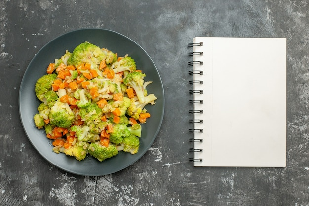 Healthy meal with brocoli and carrots next to notebook on gray table
